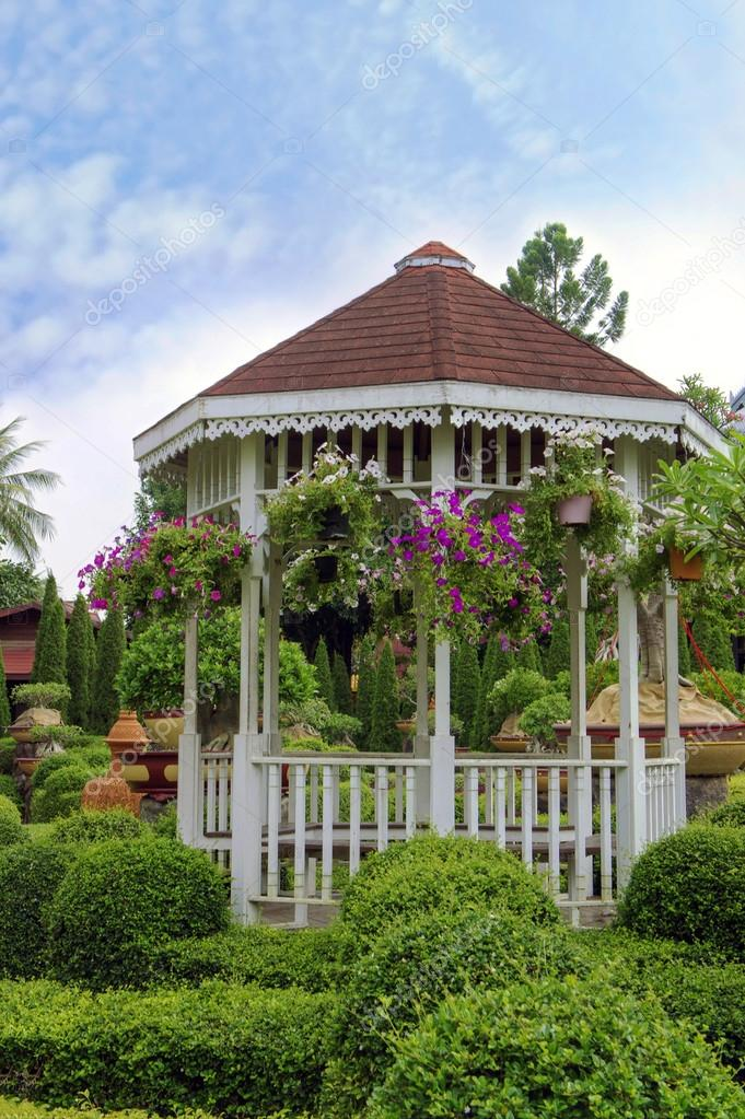 Outdoor wooden gazebo with flowers in a beautiful garden