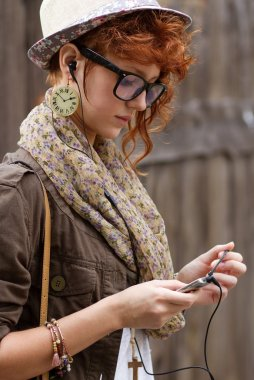 Hipster girl listening to music on mp3 player