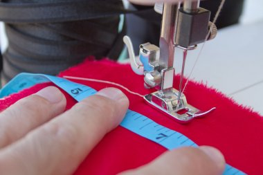 Hands of tailor sewing clothes