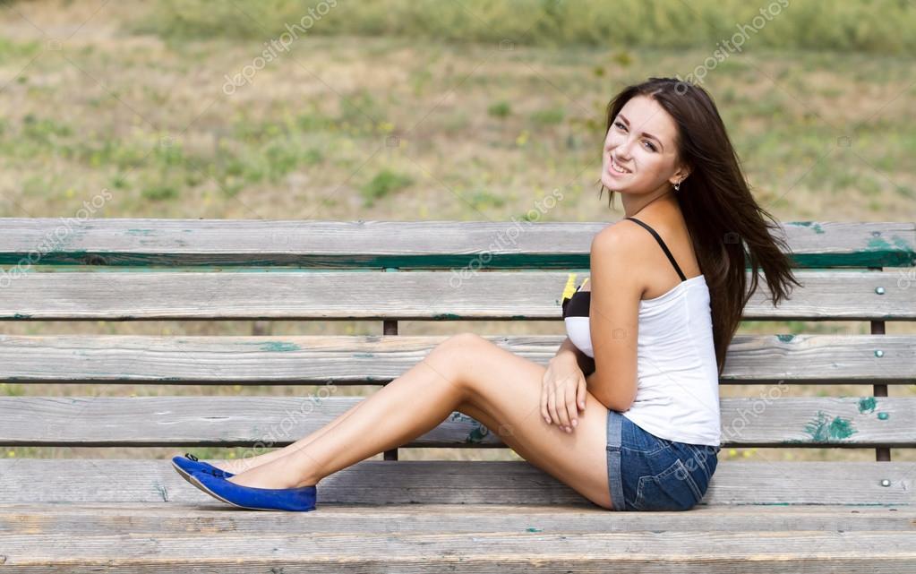Улыбающаяся девушка летом сидит на скамейке в красной юбке 14
