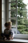 Roztomilé batole dívka při pohledu na dešťové kapky