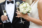 Fotografie Bride and groom holding champagne glasses
