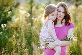 mladá matka a holčička na louce