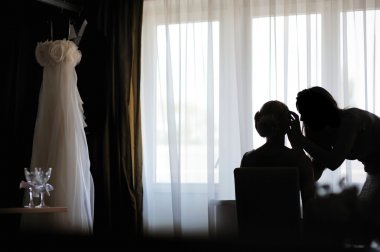 Silhouettes of a bride and a make-up artist