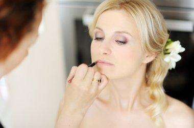 Young beautiful bride applying wedding make-up