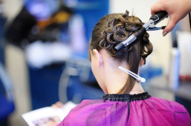 Woman's stylist's hands making a hairstyle