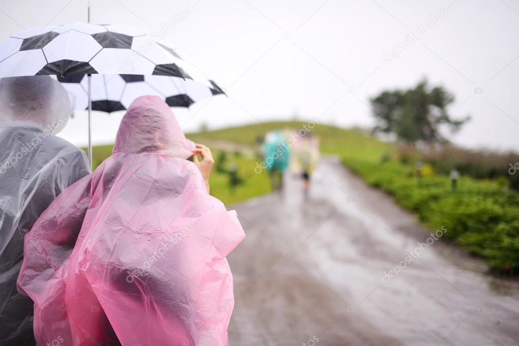 A couple in raincoats under umbrella