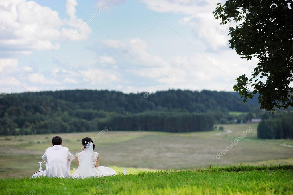Bride and groom resting outdoors