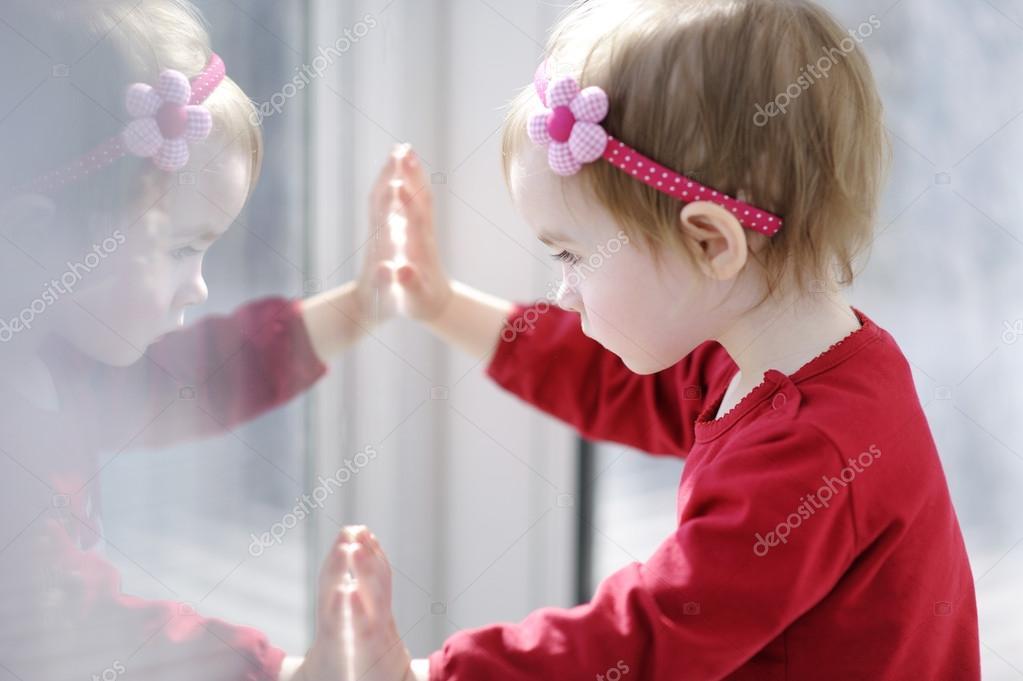 Little adorable toddler girl looking through a window