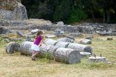 ein Mädchen besichtigt historische Ruinen des Asklepieion