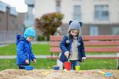 Fotografie zwei Kinder spielen in einer sandbox