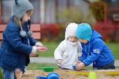 Fotografie drei Kinder spielen in einer sandbox