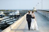 Fényképek Boldog menyasszony és a vőlegény, séta a mólón