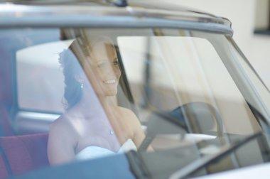 Beautiful young bride portrait in a wedding car