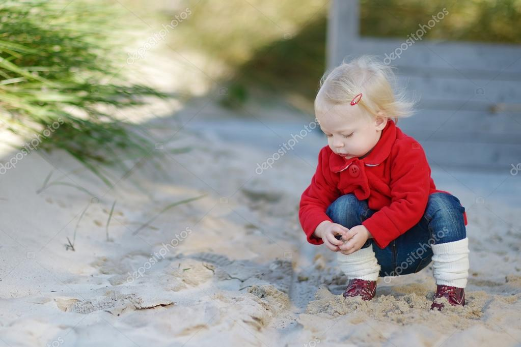 Adorable toddler girl playing in a sand