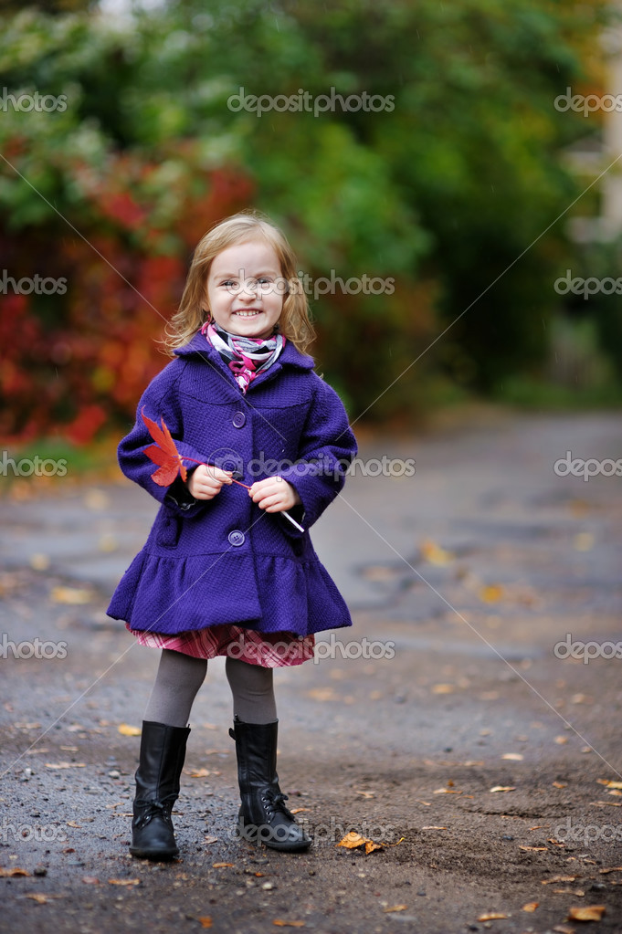 Little girl in a blue coat at autumn
