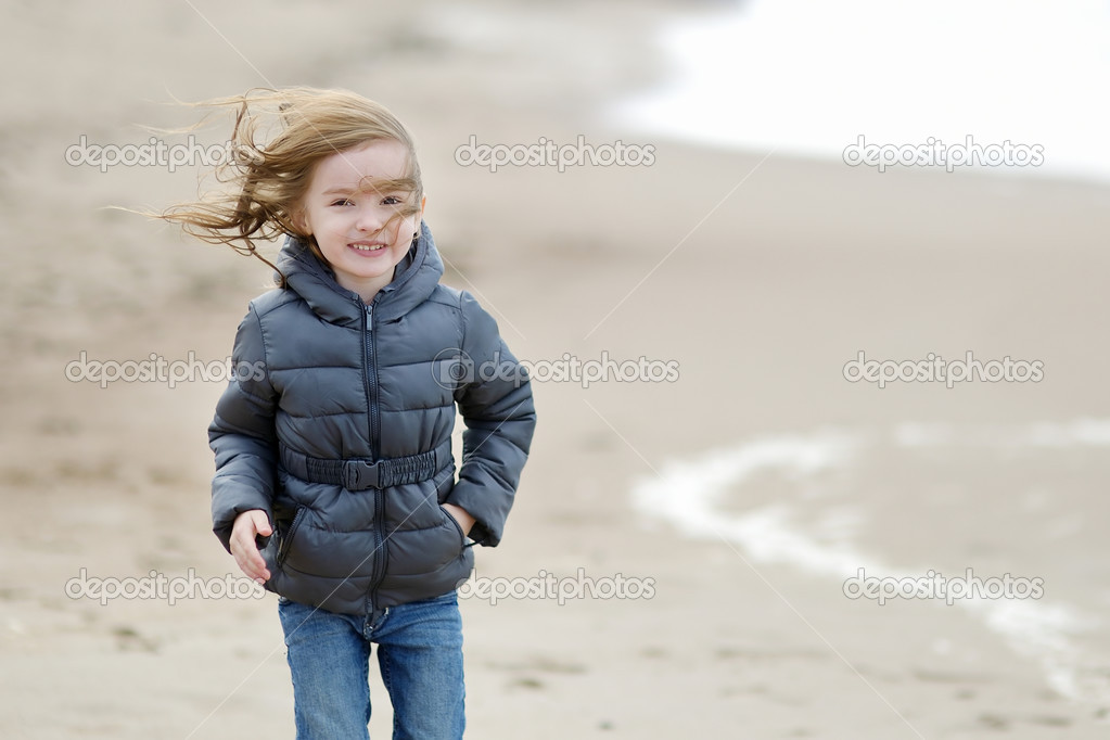 Adorable little girl walking by the seashore