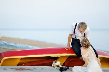 Happy bride and groom hugging by the sea