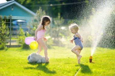 Girls running though   sprinkler