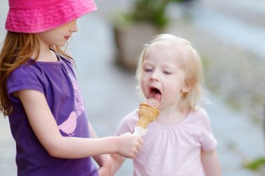 Two sisters eating ice cream