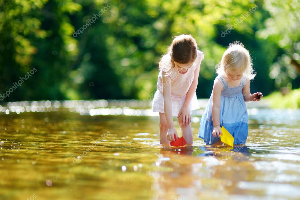Sisters playing with paper boats