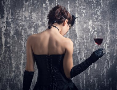 Woman in mask with red wine