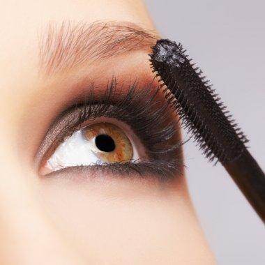 Closeup portrait of beautiful young brunette woman applying mascara stock vector