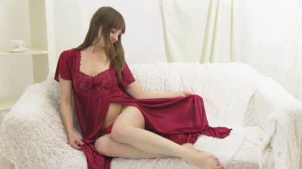 Girl in a red peignoir on sofa