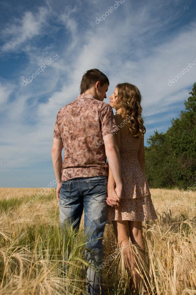 Loving couple holding hands and walking on wheat field