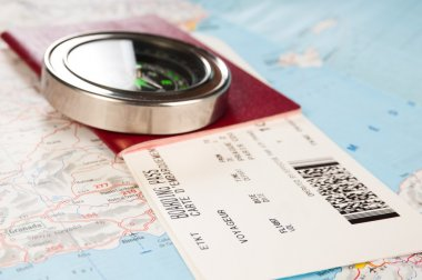 compass and passport with boarding pass