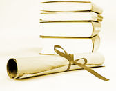 Fotografie Diploma with red ribbon and books