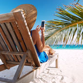 Fotografie Young woman with tablet pc at the beach