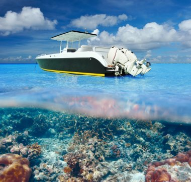 Beach and motor boat with coral reef underwater view