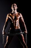 Photo Bodybuilder with chains in dark