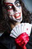 Zlý klaun s kartami v temné místnosti