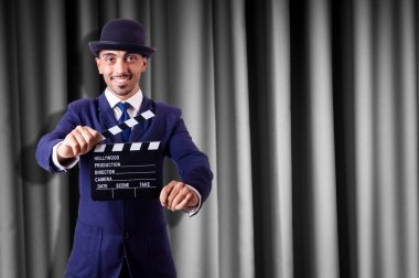 Man with movie clapper on curtain background stock vector