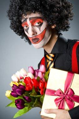 Sad clown with flowers