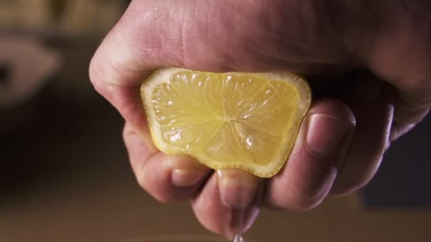 hand squeezing lemon on dark background
