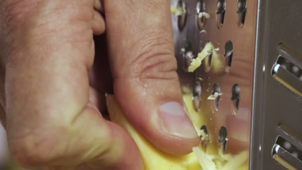 hand grating yellow cheese with a metal grater closeup