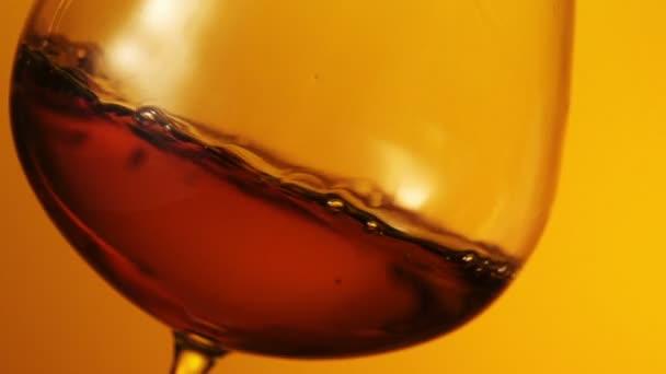 Az üveg, a vízcseppek konyak-fekete háttér