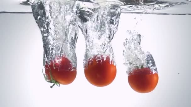 Fresh tomato dropped into water with bubbles