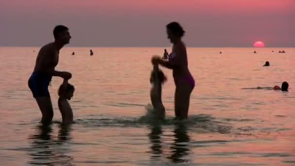 silueta rodina na moři při západu slunce