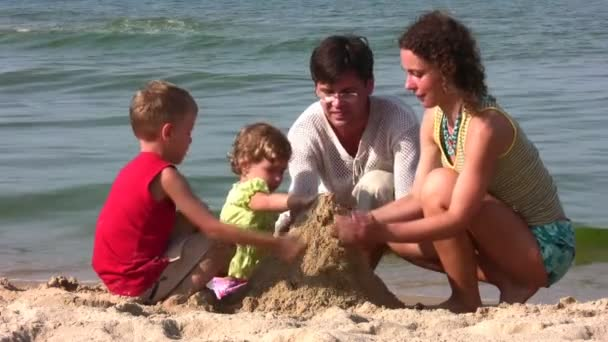 Family of four play with sand