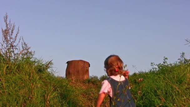 kleines Mädchen klettert auf Baumstumpf