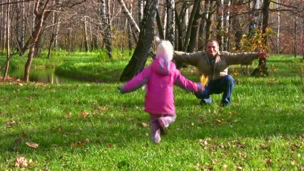 Little girl run to senior in autumn park
