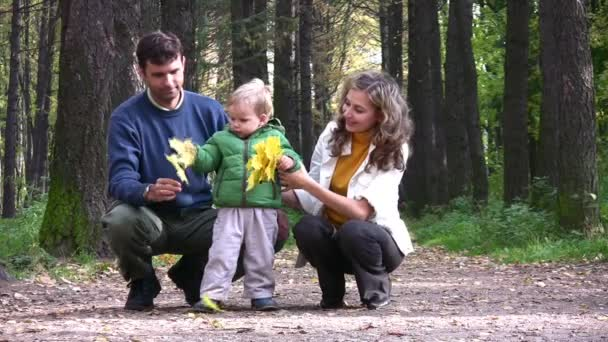 Parents with boy with leaves in park.