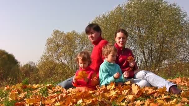 Family of four sit in autumn leaves