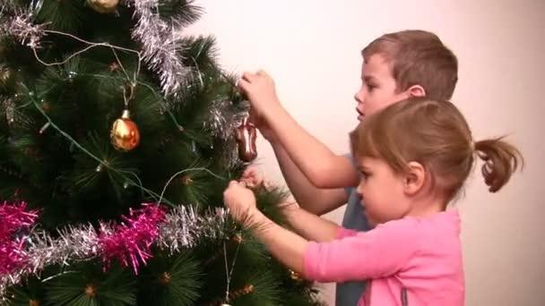 Children hangs up fur-tree toy on christmas tree