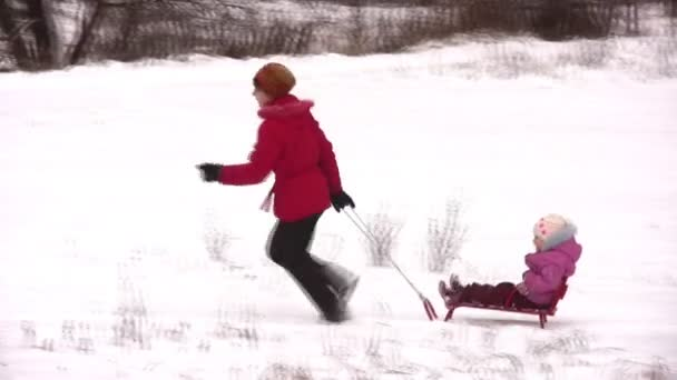 Mother with little girl on sled