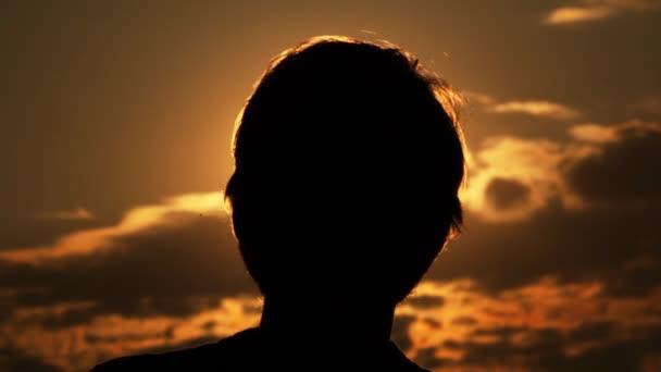 Sziluettek a fejét és a kezét a férfi ellen a nap